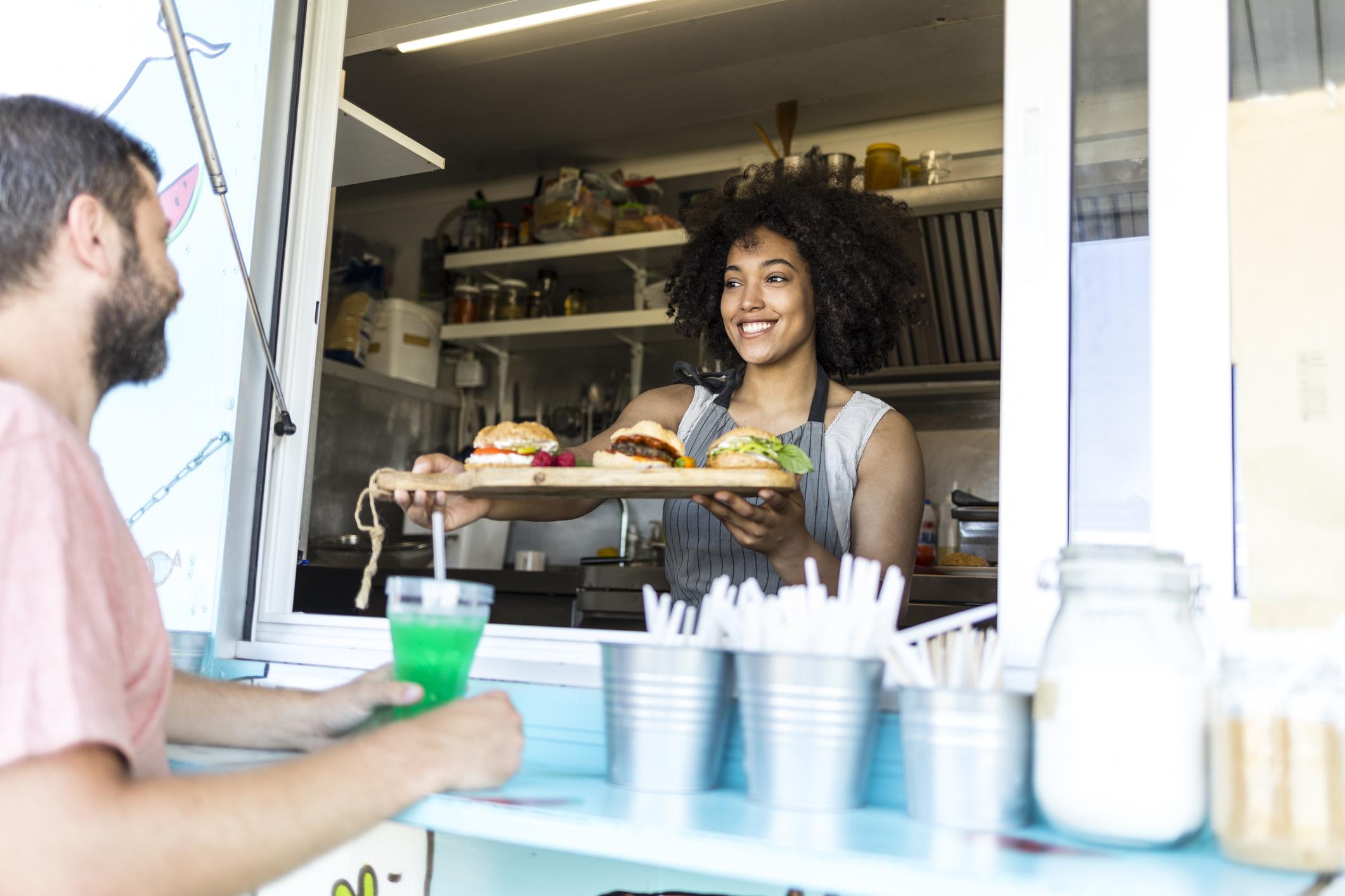 Tourist taking burgers from food van