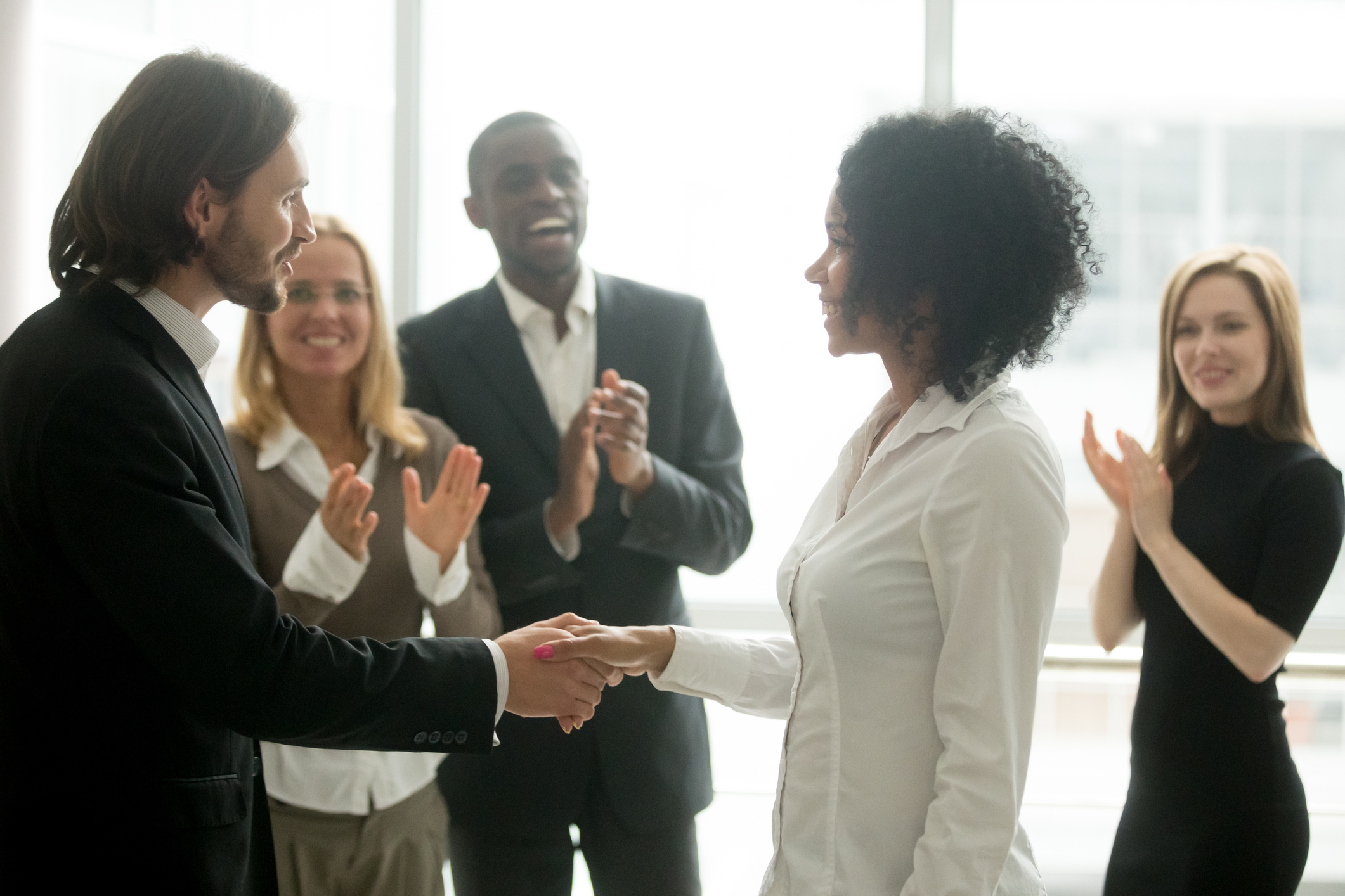 Grateful boss handshaking promoting african businesswoman congratulating with career achievement