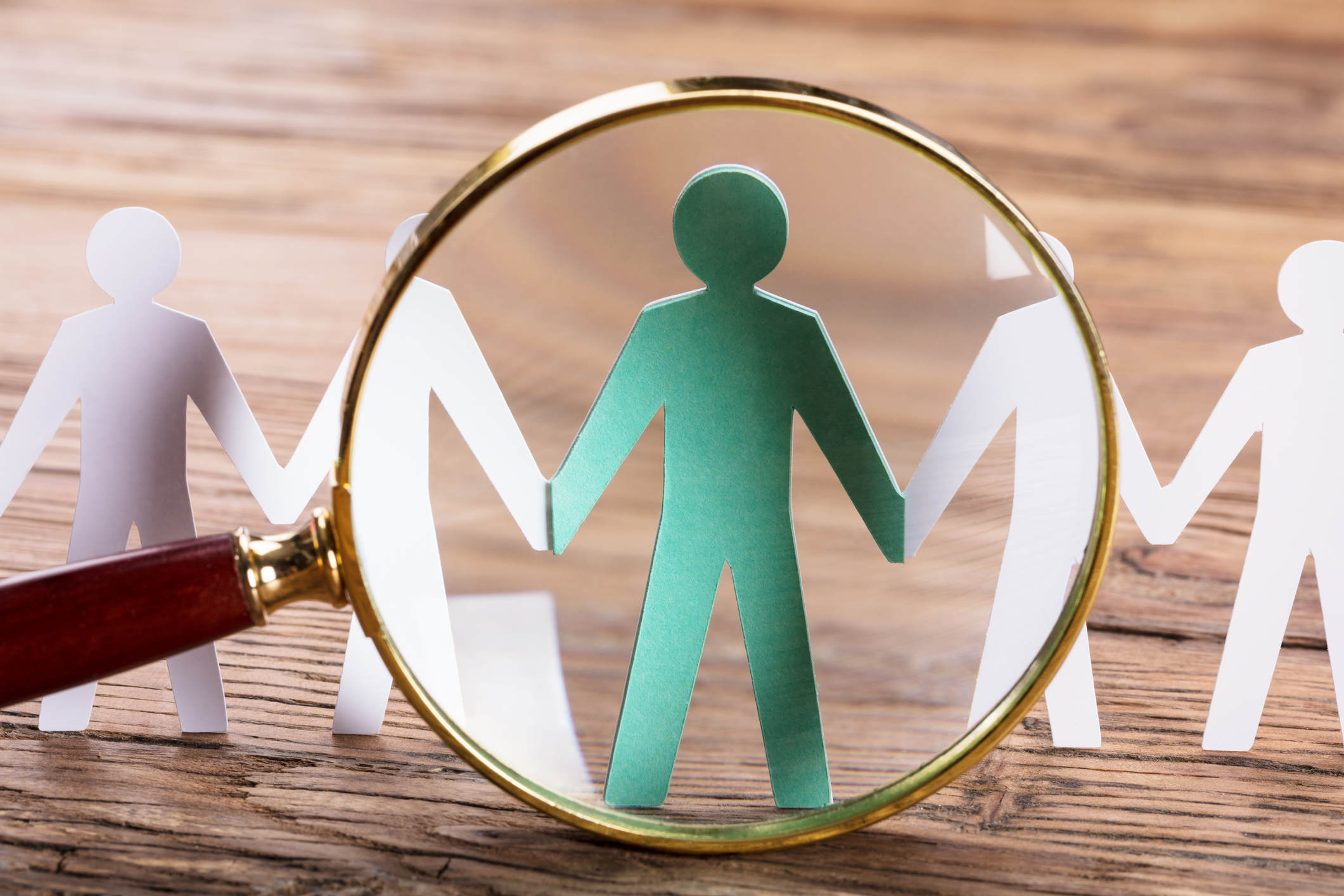 Magnifying Glass On Cut-out Figures On Wooden Desk
